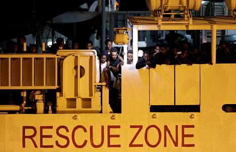 Italian rannikkovartioston merimatkalta poimimat ihmiset odottivat maahan pääsyä Cataniassa Sisilian saarella elokuun 25. päivä.
