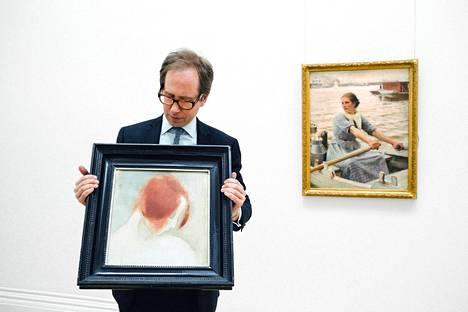 Sothebyn huutokauppakamarin taideasiantuntija Claude Piening pitelee Helene Schjerfbeckin teosta Punainen pää II. Taustalla Albert Edelfeltin sata vuotta Ranskassa piilossa pysynyt teos Maitotyttö.