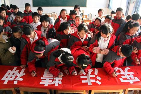 Kiinalaisen maaseutukoulun oppilaat kirjoittivat Binzhoussa nimensä banneriin, jonka teksti painottaa Kiinan perustuslain merkitystä. Kiina viettää 4. joulukuuta ensimmäistä kertaa perustuslain päivää. Kiinan kommunistinen puolue päätti teemapäivän vietosta lokakuun lopussa korostaakseen, että Kiinaa aletaan johtaa lain mukaisesti.