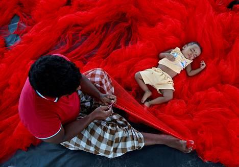 Lapsi nukkuu verkkokasan päällä samaan aikaan kun hänen isänsä paikkaa niitä intialaisessa Kochin kaupungissa tiistaina.