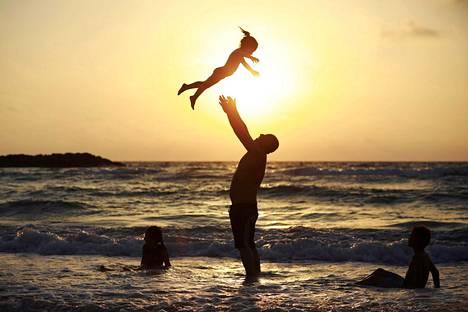 Isä heittää tytärtään ilmaan auringon laskiessa israelilaisen Ashkelonin hiekkarannalla maanantaina. Rannalle kerääntyi etenkin muslimeja juhlimaan ramadanin päättymistä.