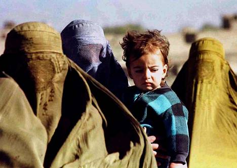 Afganistanilaisia naisia ja lapsi pakenemassa Talebanin taistelijoita kylästä Kabulin pohjoispuolelta lokakuussa 1996.