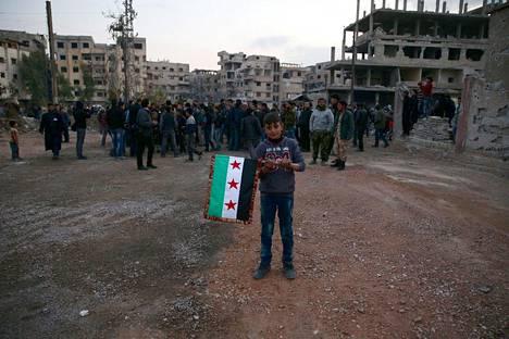Syyrialaispoika piteli opposition lippua kapinallisten hallussa olevassa Kafr Batnan kaupungissa tiistaina.