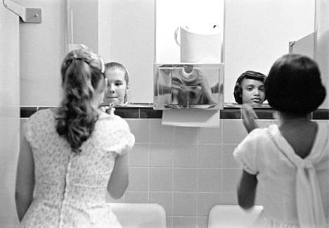 Valkoinen ja musta tyttö meikkaavat naistenhuoneessa ennen yhdentymispäivällistä Virginiassa. Yhdysvallat, 1958.
