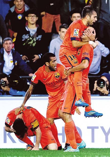 Jordi Alba on hypännyt Barcelonan maalin tehneen Sergio Busquetsin syliin. Dani Alves hoivaa pullon päähänsä saanutta Lionel Messiä.
