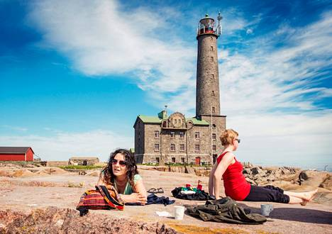 Jasmin Louhivuori (vas.) ja Sanna Pyylampi ottavat aurinkoa kalliolla Bengtskärin majakalla Suomenlahdella.