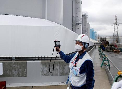 Voimalayhtiö Tepcon työntekijä seurasi säteilytasoa jäähdytysvesisäiliöiden luona perjantaina Fukushiman voimala-alueella.