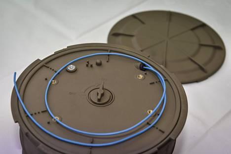 Hyppypanos kansi aukaistuna. Keskellä on vipu, jolla panos aktivoidaan. Siniseen letkuun kiinnitetään laukaisin.