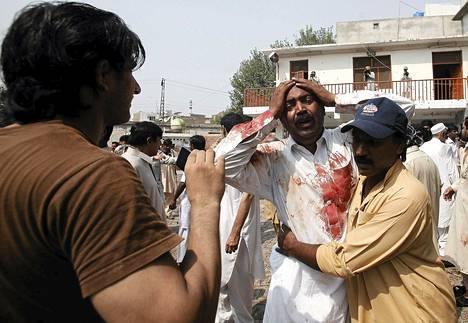 Haavoittunut mies itkee veljensä kuolemaa pommi-iskussa kirkkoon Pakistanin Peshawarissa.