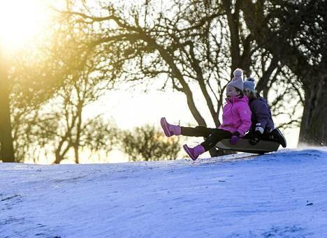 Lapset pulkkamäessä aurinkoisessa pakkassäässä Kaivopuistossa Helsingissä 9. tammikuuta.
