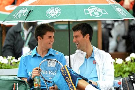 Novak Djokovic juttelee pallopojan kanssa.
