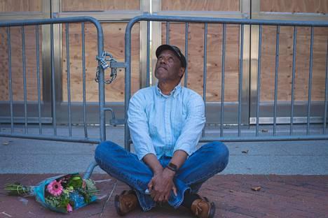 """Perjantaina menehtyneen poliisin kuolinpaikalla. """"USA on väkivallan maa. En usko että se kykenee muutokseen"""", sanoo James Collier."""