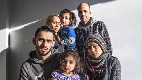Irakilainen perhe pakeni Suomeen syksyllä 2015, koska perheen isää Mohamadia (takana) kertomansa mukaan kiristettiin yhteistyöstä yhdysvaltalaisten kanssa. Edessä oikealla istuu Fatimah ja vasemmalla Nour, jonka sylissä istuu Dünya. Takana seisoo perheen isän vieressä äiti Aysar, joka kantaa Danialia.