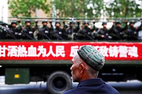 Uiguurimies katseli poliiseille lastattua kuorma-autoa Urumqissa Xinjiangissa vuonna 2014.