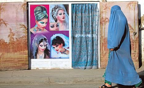 Burkaan pukeutunut afganistanilaisnainen käveli kampaamon ohitse syyskuussa Afganistanin pääkaupungissa Kabulissa.