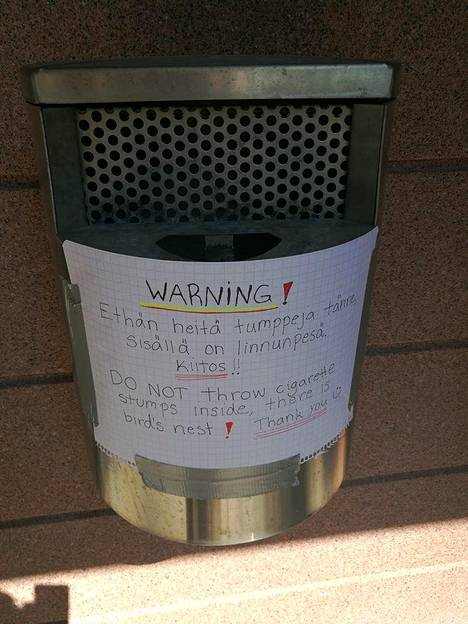 Taloyhtiön tuhka-astian sisältä löytyi linnunpesä. Bettina Reiman laittoi astian kylkeen varoituksen tupakoitsijoille.