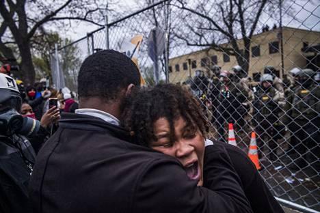Nainen näyttää itkevän mielenosoituksissa Brooklyn Centerin poliisilaitoksen edustalla.
