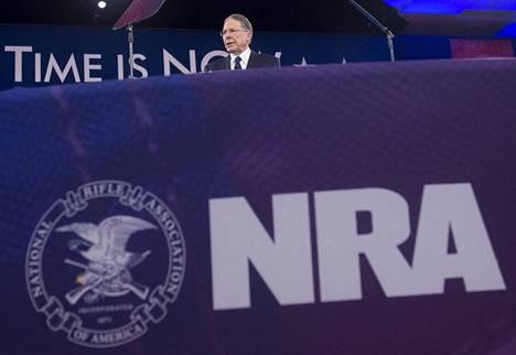 Wayne LaPierre ja NRA:n logo. Kuva on vuodelta 2016.