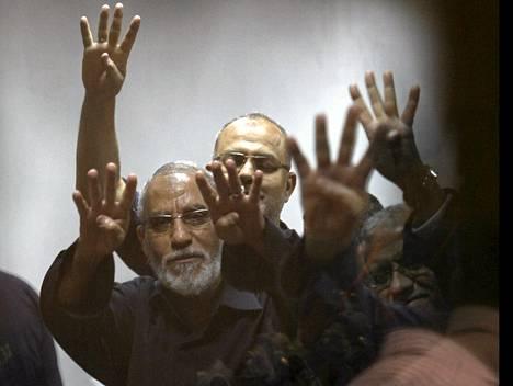 Islamistijärjestö Muslimiveljeskunnan vangittu johtaja Mohamed Badie (vas.) ja syrjäytetty presidentti Muhammed Mursi (oik.) näyttivät Rabaan aukion verilöylyä merkitsevää käsimerkkiä oikeussalissa Kairossa toukokuussa.