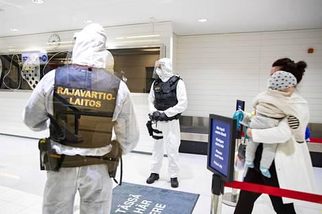 Pohjois-Makedonian Skopjesta saapuvia matkustajia ja suojavarusteisiin pukeutuneita rajavartioita Turun lentokentällä viime elokuussa. Skopjen-lennoilla oli ollut paljon matkustajia, joilla todettiin koronavirustartunta.