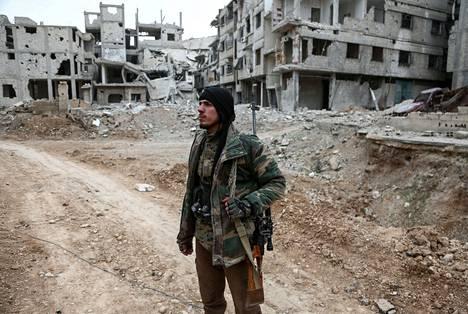 Syyrian opposition taistelija käveli tuhoutuneiden rakennusten keskellä Itä-Ghoutan Arbinissa viime torstaina.