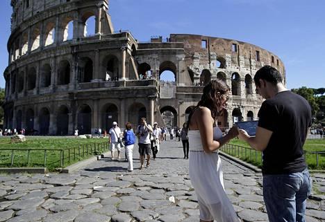 Turistit käyttivät tablettia Rooman Colosseumilla Italiassa. Italiassa on EU-tasoon nähden kallista käyttää mobiilidataa.