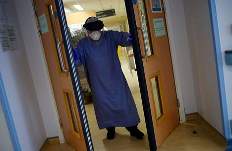 Sairaalatyöntekijä avasi teho-osaston ovet suojavarusteissa.