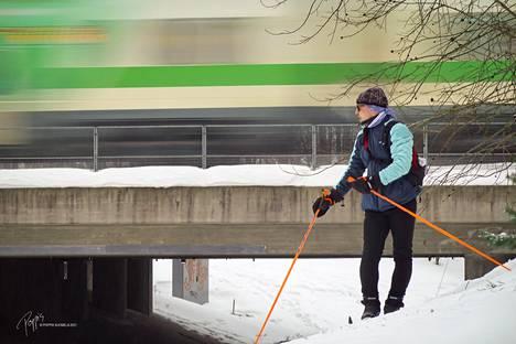 Harri Hollo hiihtämässä. Hiekkaharjussa junat kuuluvat maisemaan.