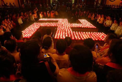 Buddhalaisen temppelin seremoniassa on aseteltu kynttilät hakaristin muotoon symboloimaan hyvää onnea.