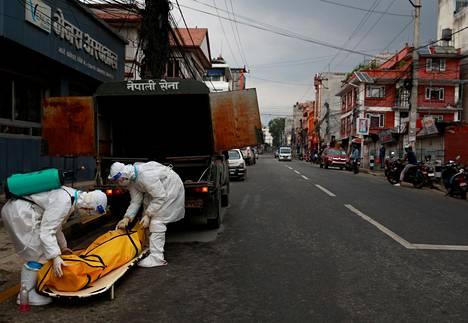 Suojapukuihin sonnustautuneet Nepalin armeijan sotilaat lastasivat koronavirukseen kuollutta autoon Kathmandussa, Nepalissa toukokuun 5. päivänä. Intiasta lähtöisin olevat virusmuunnokset leviävät nopeasti Nepalissa, jolla on pitkä yhteinen ja avonainen raja Intian kanssa.