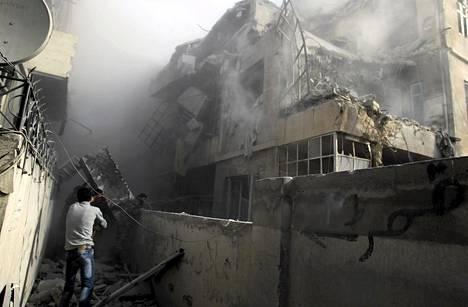 Asukkaat tutkivat pommi-iskussa tuhoutunutta taloa Aleppossa sunnuntaina.