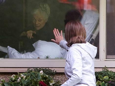 Lori Spencer heilutti koronavirustartunnan saaneelle 81-vuotiaalle äidilleen Judie Shapelle ikkunan takaa Kirklandissa Yhdysvalloissa.