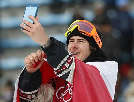 Sebastien Toutant otti selfien Kanadan lippuun kietoutuneena.