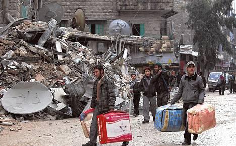 Asukkaat siirsivät tavaroitaan pommitusten tuhoamasta asuinrakennuksesta Alepposta keskiviikkona.