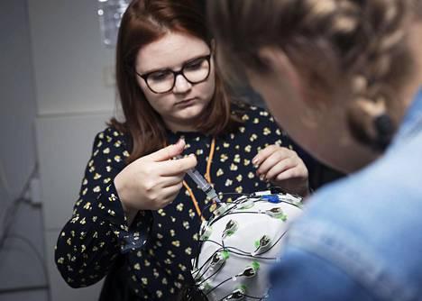 Aada Muurinen (vas.) ja Susanna Helin mittasivat EEG-laitteella, mitä koehenkilön aivoissa tapahtuu, kun ihminen kuulee sanoja.