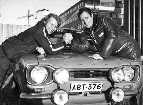 1960- ja 1970-lukujen rallipolkujen kilpakumppanit Hannu Mikkola (vas.) ja Timo Mäkinen väänsivät kättä Ford Escortin nokkapellillä.