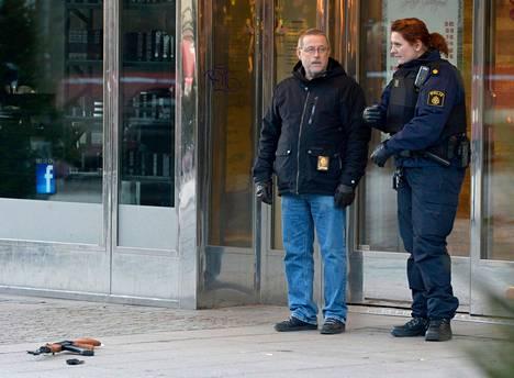 Poliisi tutki ryöstöpaikkaa Ruotsin Södertäljessä perjantaina. Haavoittuneen ryöstäjän ase oli yhä rikospaikalla.
