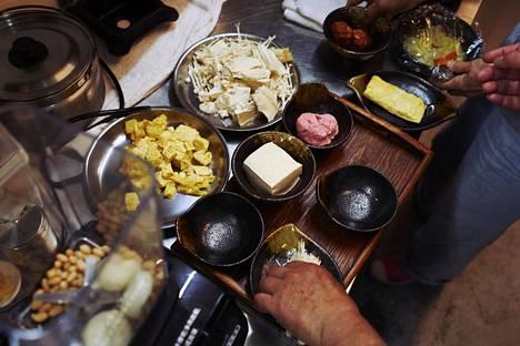 """Pääkokki Lin Xi-qing ottaa kouralliset tofua ja eri kasviksia """"jauhelihan"""" tekoon."""