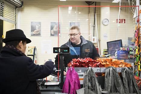 Kauppias Niko Grönberg palvelee asiakasta pleksin takaa Ruoholahdessa.