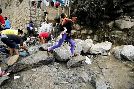 Nainen kantoi tyttöä maanvyörymän jälkeen Chosicassa Perussa tiistaina. Rankkasateiden aiheuttamassa maanvyörymässä sai surmansa ainakin seitsemän ihmistä.