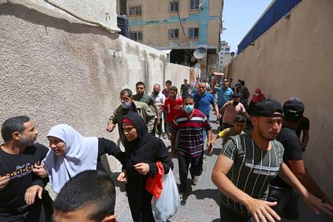 Gazalaiset pakenivat rakennuksesta Israelin hävittäjien pommitusten aikana tiistaina.
