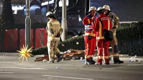 Pelastusviranomaiset ja palomiehet keskustelivat joulutorille syöksyneen rekan vieressä Breitscheidplatzilla maanantai-iltana.