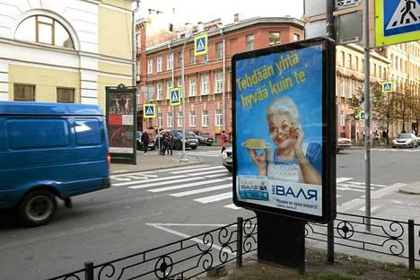 """""""Tehdään yhtä hyvää kuin te"""", mainoksessa Suomen pääkonsulaatin lähistöllä ilmoitettiin. Mainoksen alareunassa sama lukee venäjäksi."""