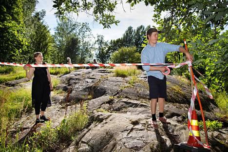 Hanna Lammi ja Olli Leskisenoja kiinnittävät eristysnauhaa kallioalueen reunalle. Aktiivit havainnollistavat tulevan päiväkodin haukkaamaa tilaa aitaamalla alueen.