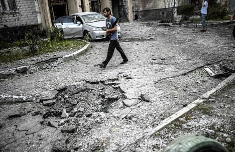 Venäjän-mielinen taistelija kulki kranaatti-iskun tuhoaman pihan halki Donetskissa 29. heinäkuuta.