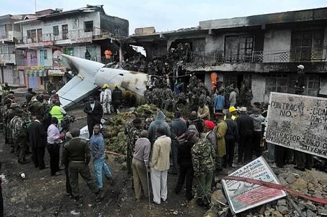 Pelastajia ja katselijoita onnettomuuspaikalla nairobilaisessa lähiössä jossa Somaliaan lähtenyt khatlastissa ollut rahtikone Fokker 50 törmäsi liiketaloon keskiviikkona.