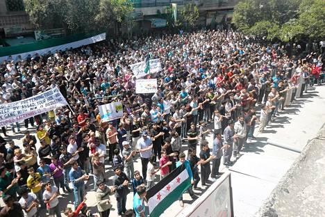 Syyrian oppostion välittämässä kuvassa syyrialaiset osoittivat mieltään presidentti Bashar Al-Assadia vastaan Kfarnabelin kaupungissa perjantaina.