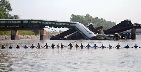 Pakistanin armeijan sotilaat kulkivat käsikkäin kanaalissa Gujranwalan läheisyydessä tapahtuneen junaturman jälkeisessä etsintäoperaatiossa.