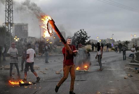 Palestiinalaismies osoittaa mieltään Israelia vastaan lähellä Bet Elin juutalaissiirtokuntaa Länsirannalla.