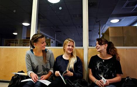 """Vantaan Simonkylän koulussa on säästetty energiaa valaistusta säätämällä. Karoliina Jaskari (vas.), Saara Hänninen ja Mira Jaskari ovat tyytyväisiä, ettei taustalla olevassa kirjastossa pala valo, kun siellä ei ole ketään. He uskovat, että energiansäästö koituu luonnon hyväksi. """"On sitten metsiä silloinkin, kun olemme vanhoja"""", Hänninen miettii."""